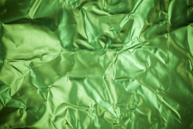 Fondo de papel de aluminio verde arrugado.