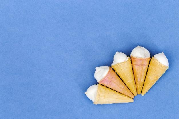 Fondo de papel de pequeños conos de helado con espacio de copia. vista desde arriba. fondo de verano estilo de minimalismo.