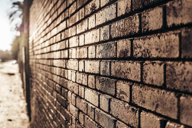 El fondo de la pared de ladrillo en la puesta del sol con los rayos del sol, textura de piedra.