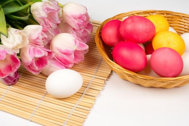 Fondo de pascua, huevos coloridos y blancos con ramo de tulipanes