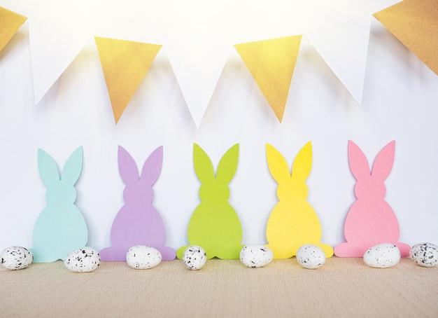 Fondo de pascua con huevos, conejos y banderas de garland.