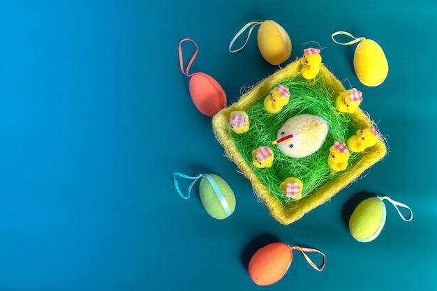 Fondo de pascua con huevos de pascua y pollos amarillos esponjosos. vista superior