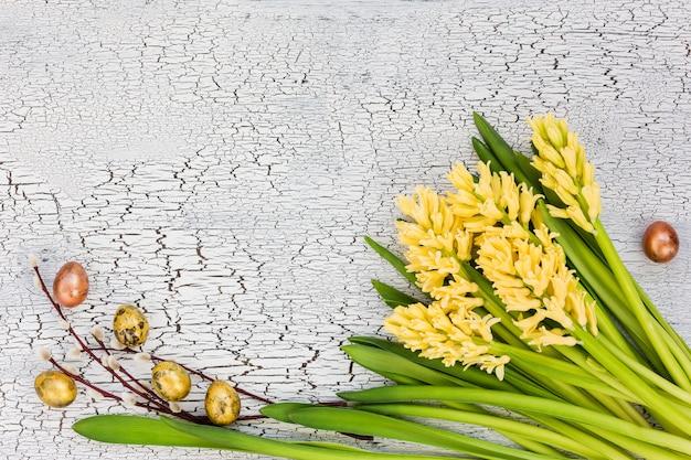 Fondo de pascua jacintos, huevos de codorniz y rama de sauce amarillos en mesa de madera azul.