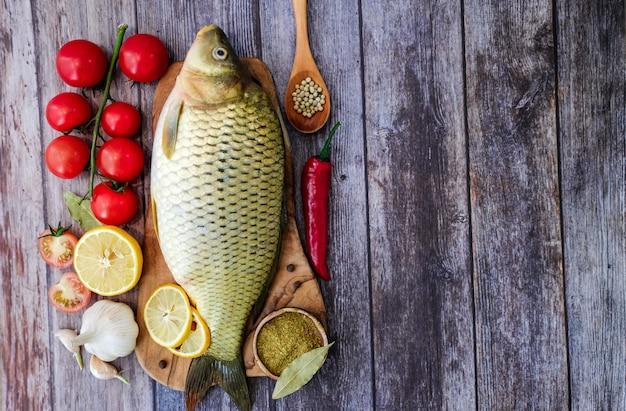 Fondo de pescado fresco listo para cocinar. carpa en una cocina de madera tablero en la cocina rodeado de verduras (pimiento, ajo, tomates cherry, limón).