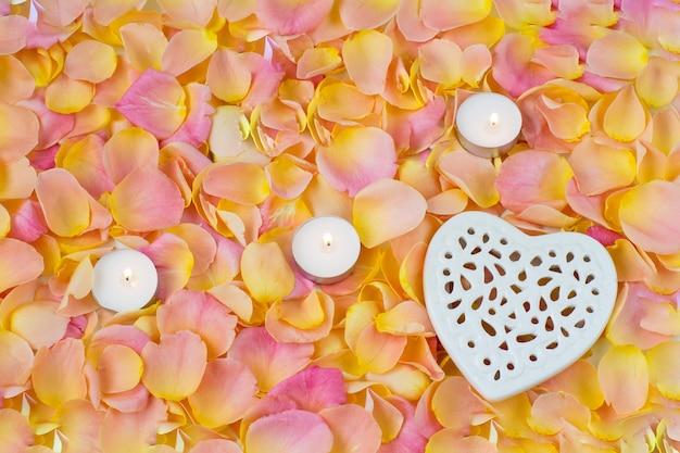 Fondo de pétalos de rosa color de rosa, corazón de cerámica tracería y tres velas