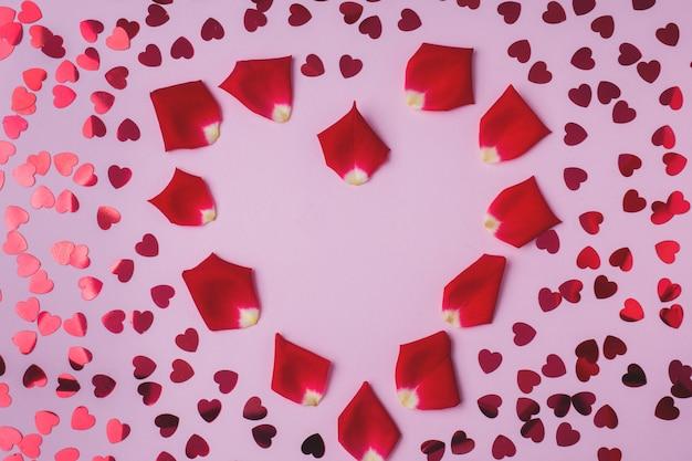 Fondo de pétalos de rosa y corazones rojos.