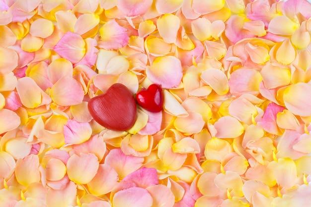 Fondo de pétalos de rosa rosa y dos corazones rojos