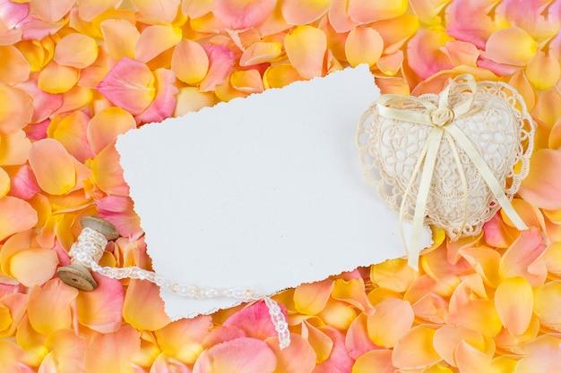 Fondo de pétalos de rosa rosa, hoja de papel, corazón de encaje y cinta