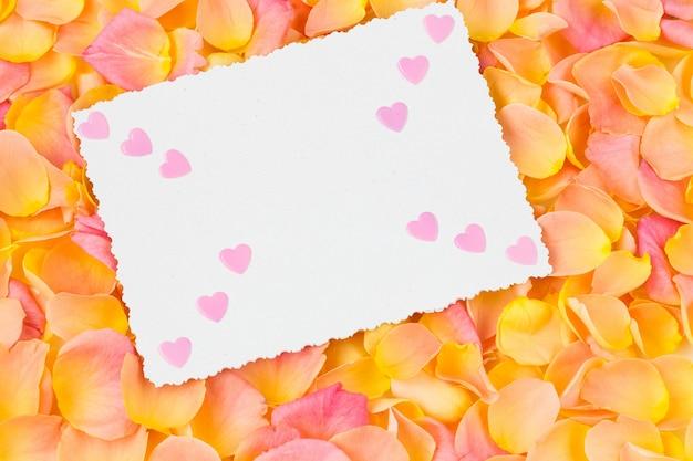Fondo de pétalos de rosa rosa, hoja de papel y corazones rosados