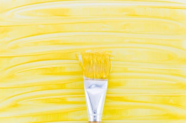 Fondo de pintura amarilla con pincel