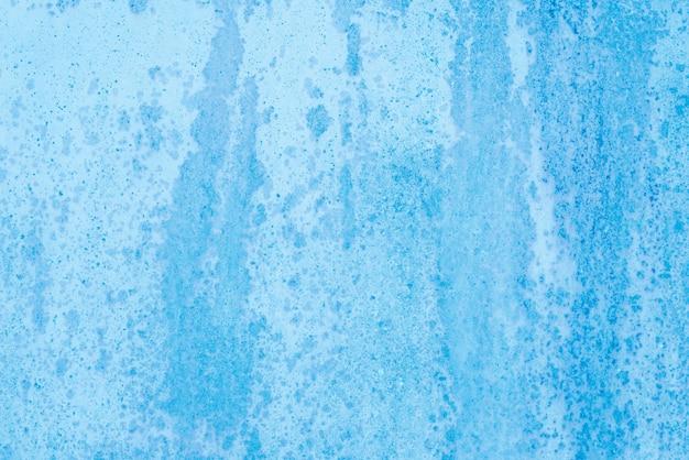 Fondo de pintura azul no uniforme sobre superficie metálica