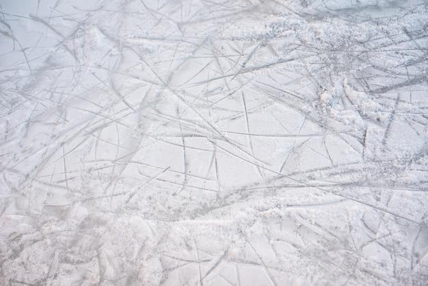 Fondo de piso de una pista de hielo congelado con marcas de patines, con nieve blanca durante el invierno.