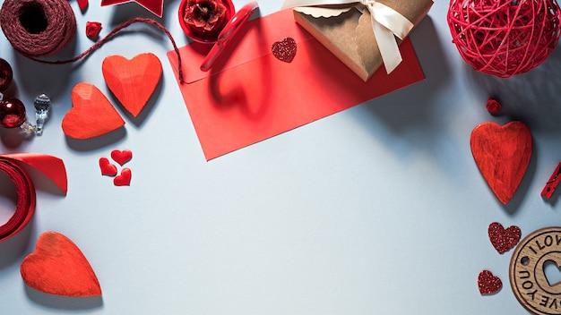 Fondo plano del día de san valentín con corazones, sobre y decoración Foto Premium