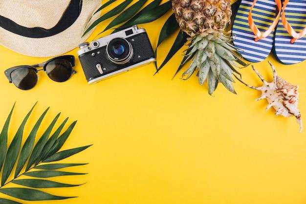Fondo plano de verano pone. hojas de palma, chancletas, piña, lentes de sol, cámara, sombrero de paja y cáscara sobre fondo amarillo.