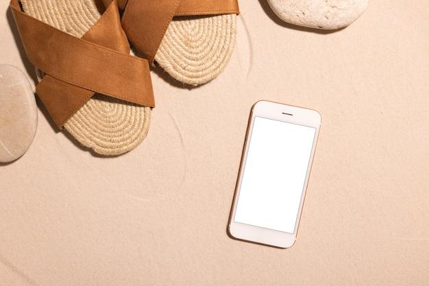 Fondo de playa con sandalias marrones de teléfono móvil y piedra en una playa de arena en el concepto de sol verano ...