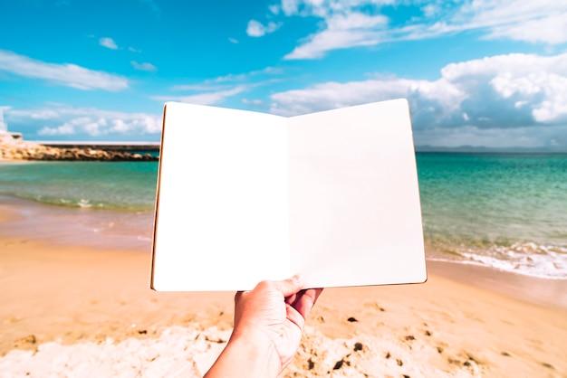 Fondo de playa de verano con un cuaderno en blanco