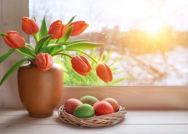 Fondo de primavera con hierba y tulipanes en el tablero de la ventana en una puesta de sol después de la lluvia