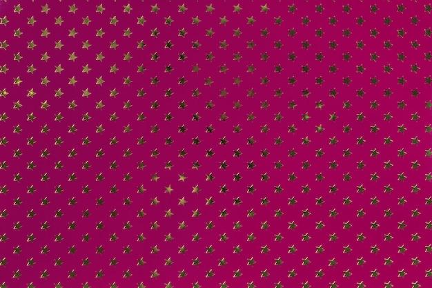 Fondo púrpura oscuro de papel de aluminio con un patrón de estrellas doradas.