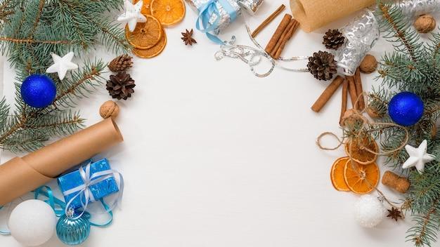 Fondo de ramas de árboles de navidad, bolas de navidad blancas y azules y naranja seca sobre una mesa de madera