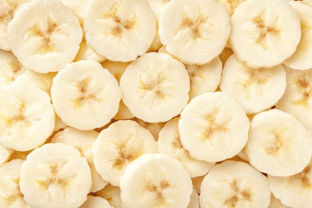 Fondo de las rebanadas cortadas maduras del plátano, primer.