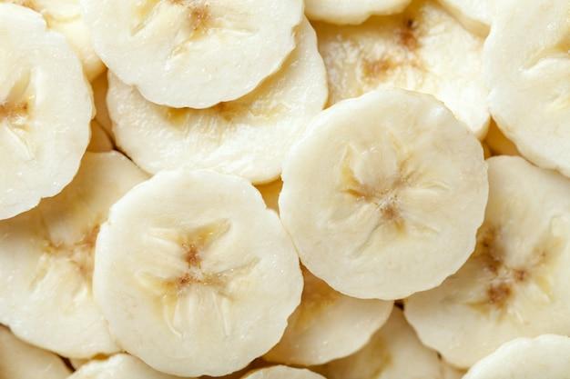 Fondo de las rebanadas maduras cortadas del plátano, primer.