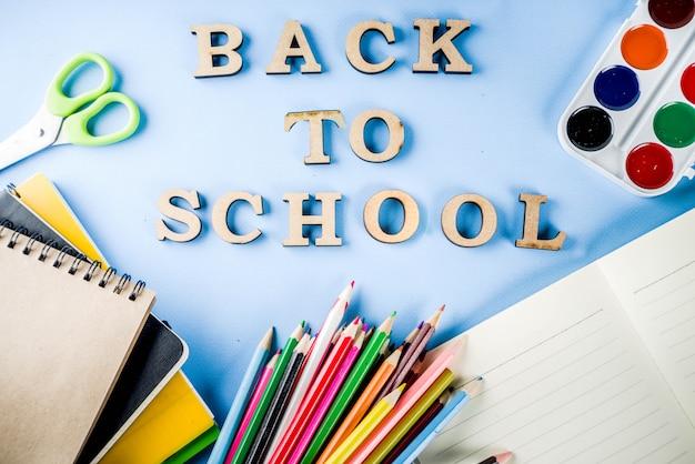 Fondo de regreso a la escuela con accesorios para el aula: pinturas, lápices, cuadernos, libros, tijeras, tiza, marcadores, fondo azul, espacio de copia superior