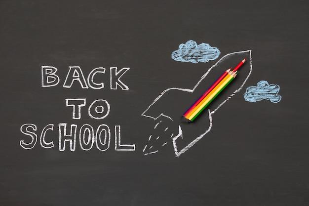Fondo de regreso a la escuela con dibujo de cohete y lápices sobre pizarra.
