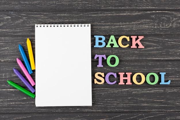 Fondo de regreso a la escuela con lápices de colores y cuaderno