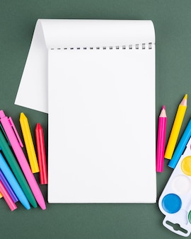 Fondo de regreso a la escuela con lápices de colores y espacio de copia en el cuaderno