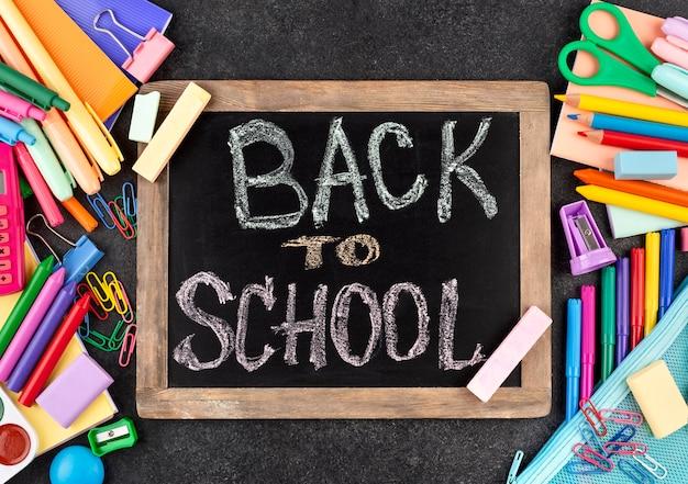 Fondo de regreso a la escuela con útiles escolares en pizarra