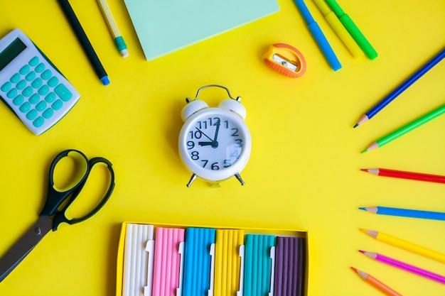 Fondo de regreso a la escuela, útiles escolares y relojes sobre un fondo amarillo, plano
