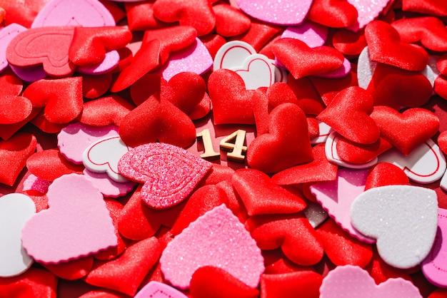 Fondo rojo para el día de san valentín, día 14, lleno de corazones rojos.