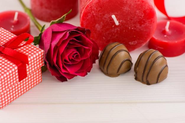 Fondo rojo del día de tarjetas del día de san valentín con las rosas y el chocolate rojos en una tabla de madera blanca.