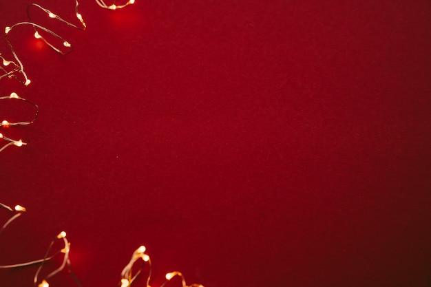 Fondo rojo con luces iluminadas de guirnalda