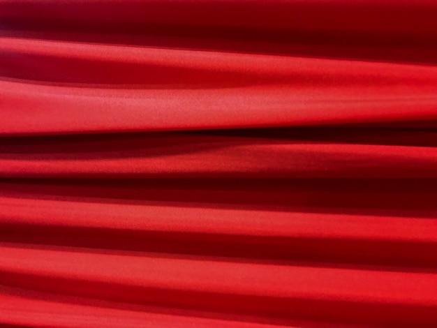 Fondo rojo lujoso horizontal de la textura del paño de la tela de la curva que teje.