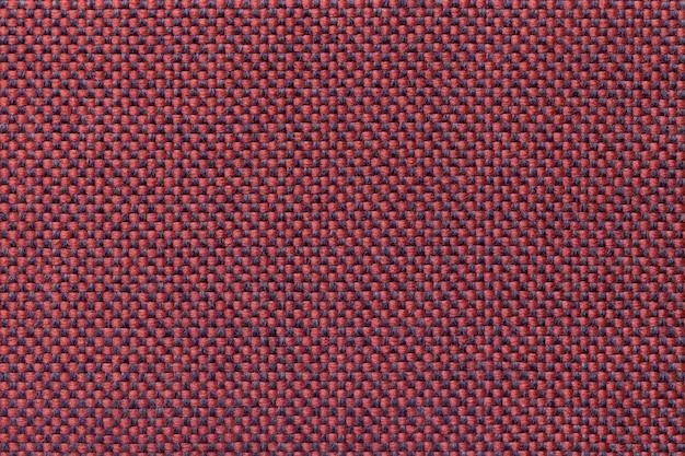 Fondo rojo oscuro de la materia textil con el modelo a cuadros, primer. estructura de la macro de la tela.