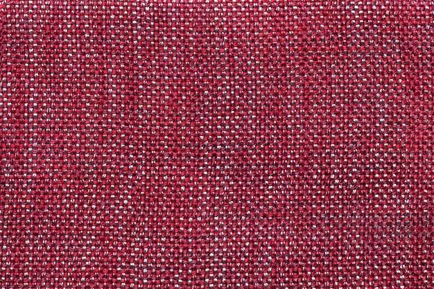 Fondo rojo oscuro de la materia textil con el modelo a cuadros, primer.