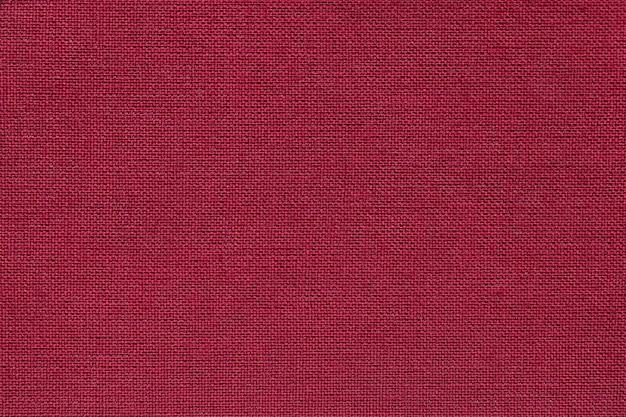 Fondo rojo oscuro de un material textil con patrón de mimbre, primer plano.