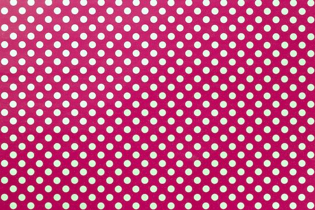 Fondo rojo oscuro de papel de regalo con un patrón de lunares dorados closeup.