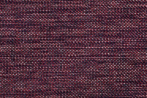 Fondo rojo oscuro textil con diseño a cuadros, primer plano. estructura de la macro de la tela.