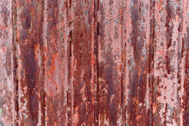 Fondo rojo oxidado con pintura descascarada.