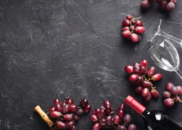 Fondo rojo vino con uvas, botella y vasos, marco en textura negra y oscura, espacio de copia, vista superior