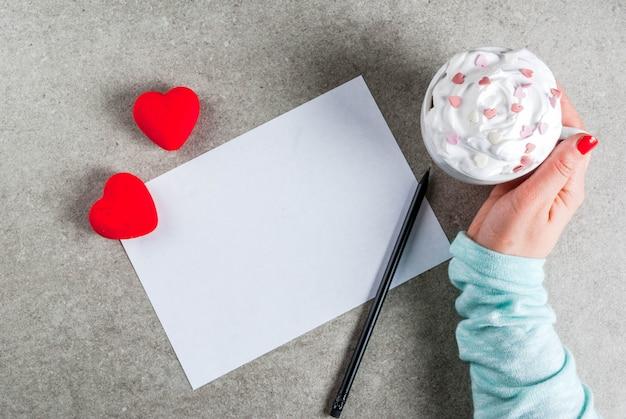 Fondo romántico día de san valentín chica escribiendo (mano en imagen) en papel en blanco para carta felicitaciones chocolate caliente con crema batida y corazones dulces