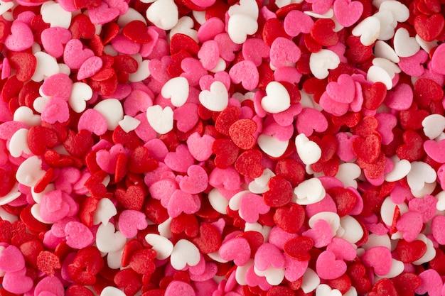 Fondo romántico, vista superior de un grupo de caramelos en forma de corazón rojo, blanco y rosa
