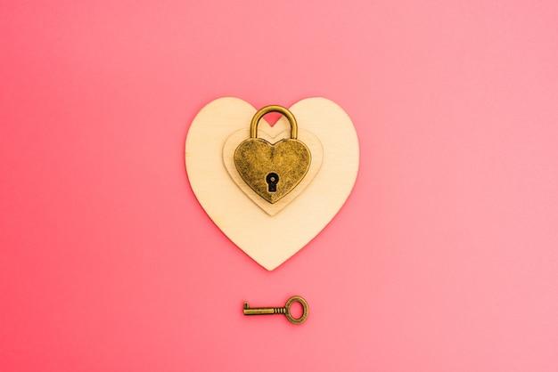 Fondo rosa con candado romántico en forma de corazón, concepto de amor encadenado.