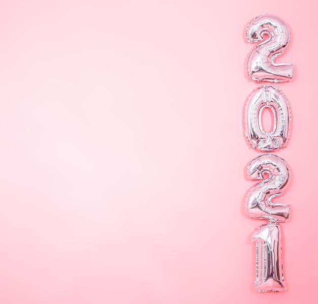 Fondo rosa claro con globos plateados de año nuevo en forma de números en el lado derecho, concepto de año nuevo