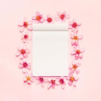 Fondo rosa con cuaderno alrededor de flores