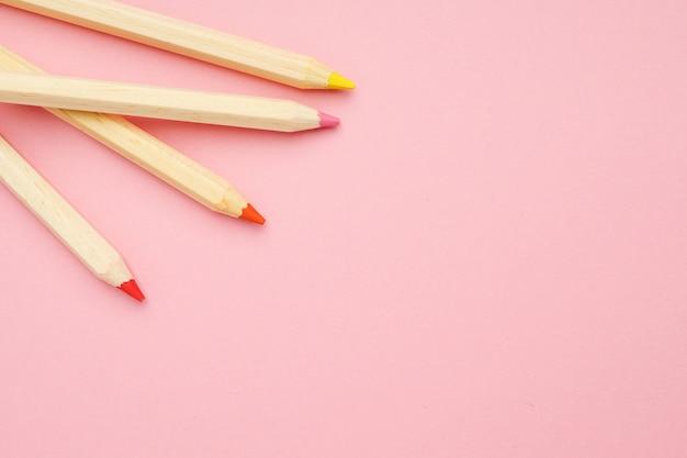 Fondo rosa con lápices de colores ordinarios de madera. de vuelta a la escuela.