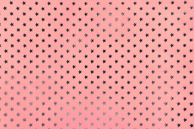 Fondo rosa de papel de aluminio con un patrón de estrellas plateadas