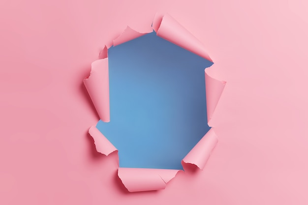 Fondo rosa rasgado rasgado con agujero en el centro para su contenido publicitario o promoción.